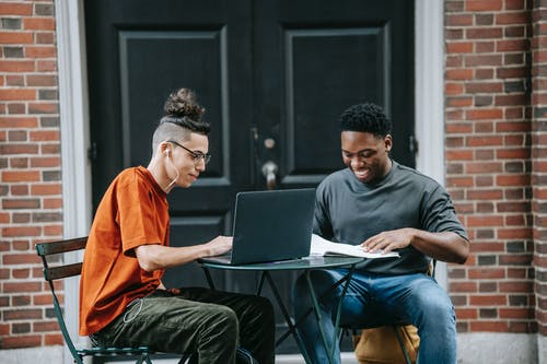 Positive young diverse male colleagues in casual clothes smiling and using laptop while working remotely on project sitting at table in street cafe
