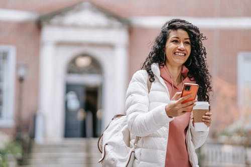 Cheerful young ethnic female student with long curly hair in casual clothes and backpack smiling and looking away while using mobile phone standing in campus with takeaway coffee
