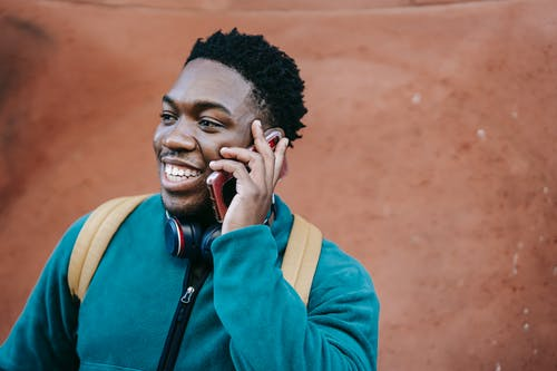 Joyful young black guy talking on smartphone on street