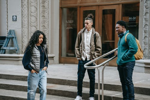 Young ethnic outcast female walking on street near diverse bullying male classmates standing on building stairs and smiling