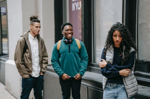 Upset young ethnic female student being bullied by diverse classmates on street