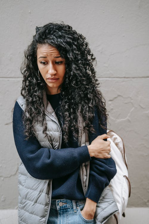 Upset young ethnic female with long curly hair in casual outfit standing on street and looking down thoughtfully