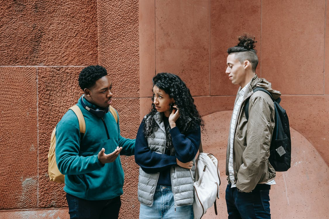 Diverse teens chatting on street after studies