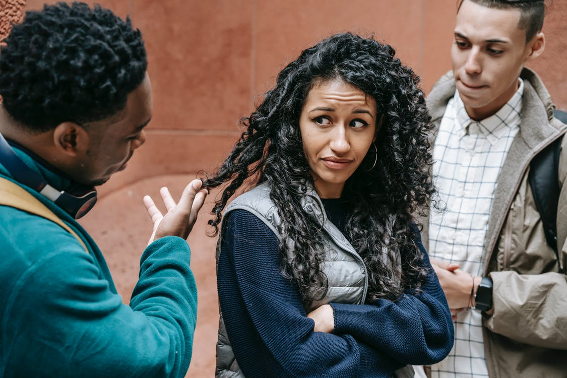 Frightened young ethnic female standing on street with crossed arms and looking at African American abusing male groupmate