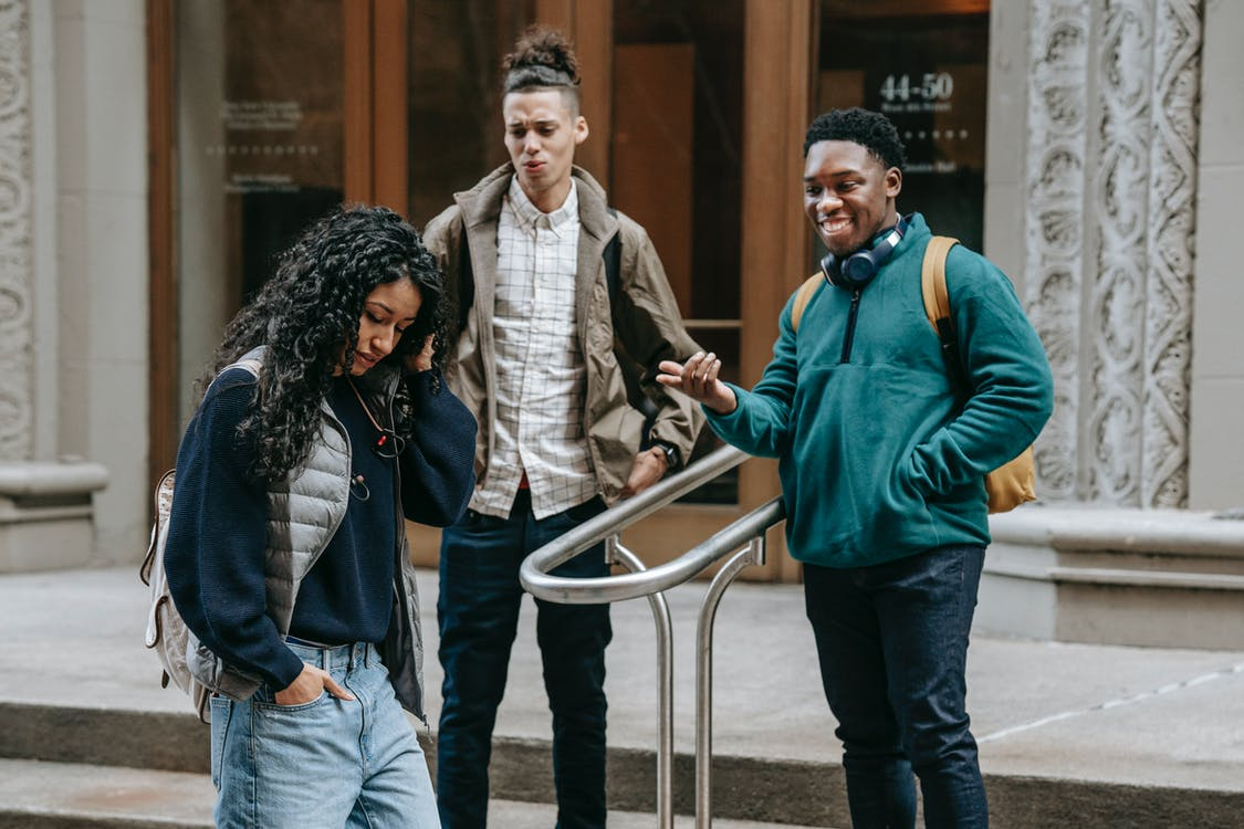 Happy young diverse guys gazing on ethnic female walking on street
