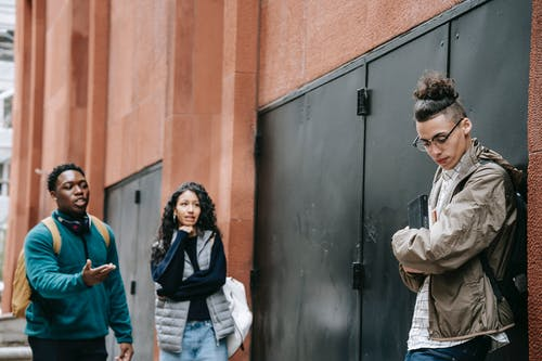 Bullied ethnic guy leaning on wall near rebellious multiracial classmates