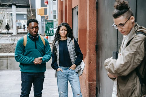 Young multiethnic students gossiping about sad male groupmate leaning on wall on street and looking down