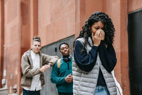 From below of despaired young ethnic female student covering mouth with hands while crying on street after being bullied by multiracial classmates