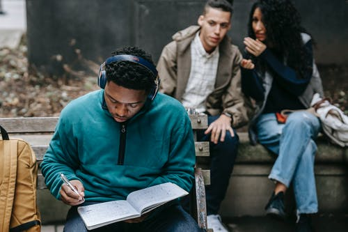 Crop young ethnic man and woman sitting on bench and gossiping about concentrated African American male student listening to music in headphone and doing homework assignment