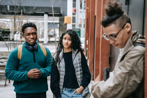 Young black guy and ethnic lady scoffing at shy upset male classmate while standing together on city street