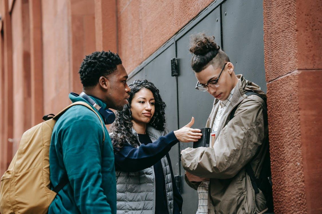 藍色夾克的男人親吻女人的黑色和棕色外套