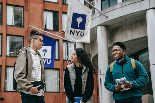 Group of diverse friends in casual clothes with papers standing near building and discussing details of university project