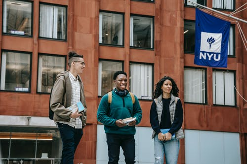 Group of happy multiracial friends with backpacks and notebooks smiling while standing near building and talking