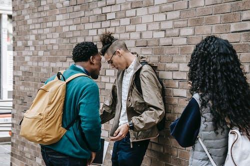 Classmates bullying student near brick wall