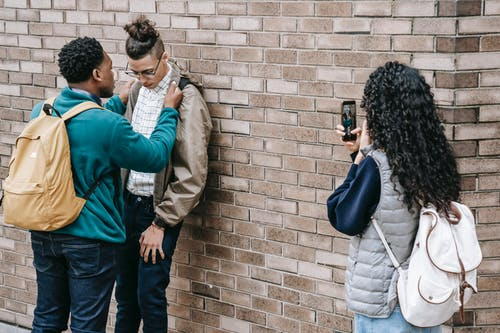Diverse friends bullying classmate near building