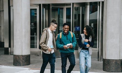 Smiling young multiracial group of friends in casual outfits and backpacks strolling with books and talking on city street near building with columns and glass doors in daylight