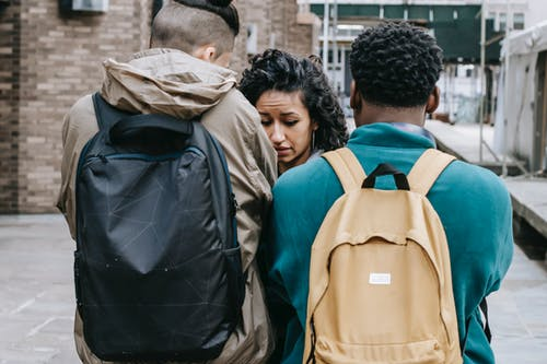 Multiracial young men bullying young woman on street