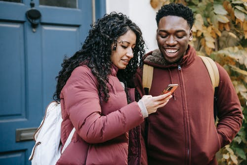 Multiethnic happy couple smiling and checking smartphone on street