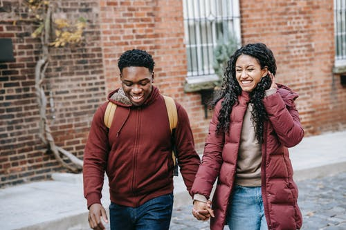 Multiethnic young glad couple holding hands and smiling while promenading near brick building on urban street