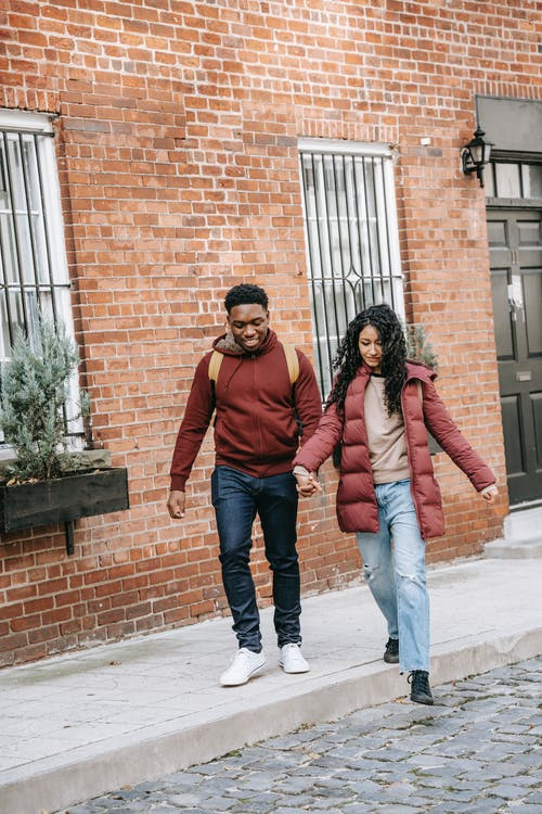 Young diverse delighted couple holding hands and walking on street