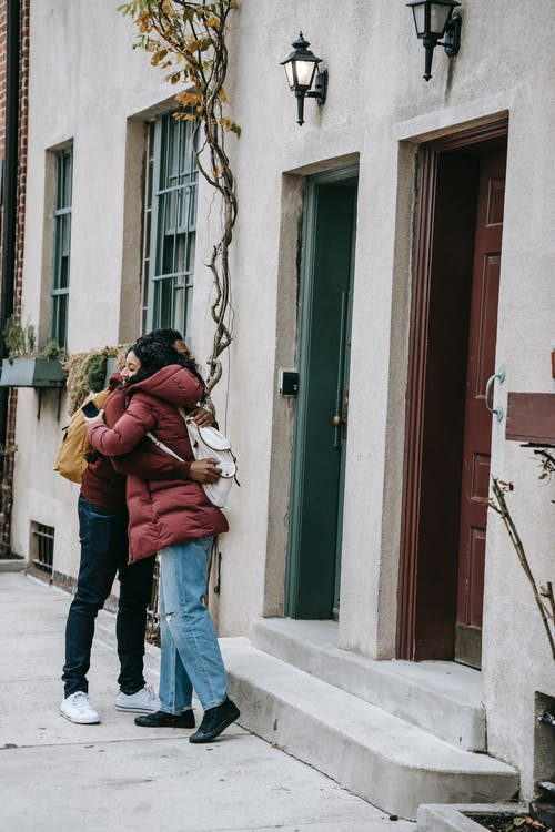 Glad young diverse couple embracing near building