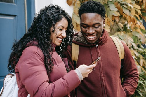 Cheerful diverse couple smiling and sharing smartphone