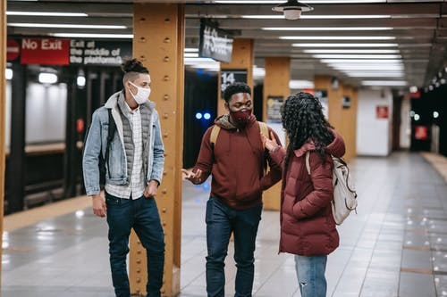 Multiracial group of friends with backpacks wearing protective masks looking at each other while standing on subway station during meeting