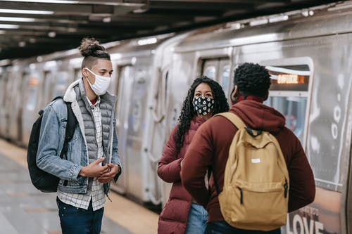 Multiethnic friends in protective masks chatting on train station
