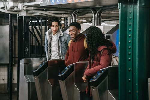 Positive multiethnic group of friends in warm clothes walking through automatic metal gates in subway platform while entering railway station