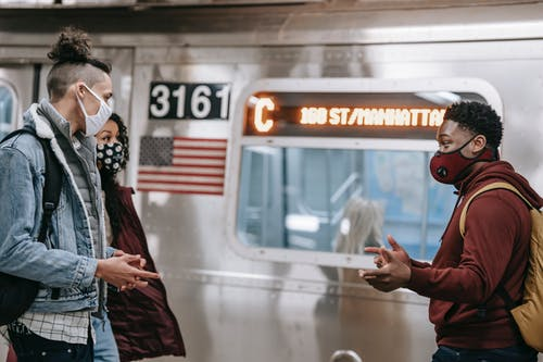 Multiracial friends in masks talking on train platform
