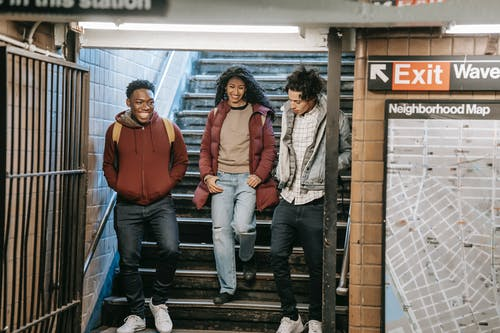 Happy multiethnic friends walking down stairs in underground station