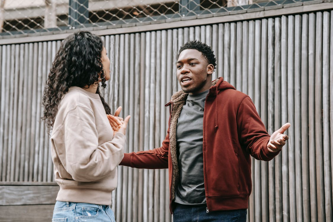 Angry African American boyfriend and ethnic girlfriend looking at each other while having emotional dispute on street near wooden fence
