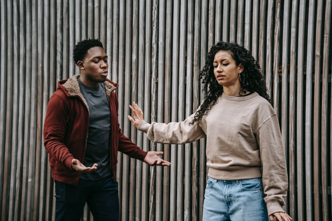 Insulted ethnic girlfriend with outstretched arm and irritated African American boyfriend having quarrel near wooden wall on street during breakup