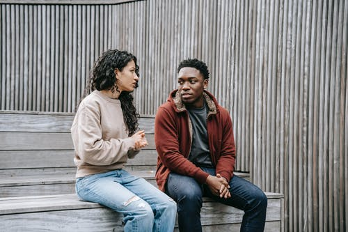 Unsatisfied multiethnic couple having conversation on stairs