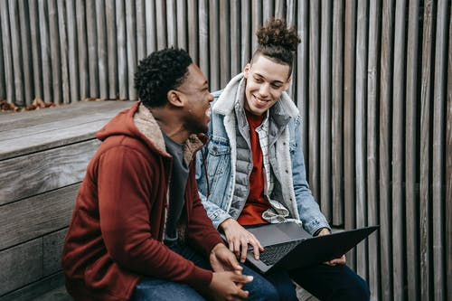 Cheerful multiracial students talking and smiling while surfing internet on netbook on wooden stairs near fence in daytime