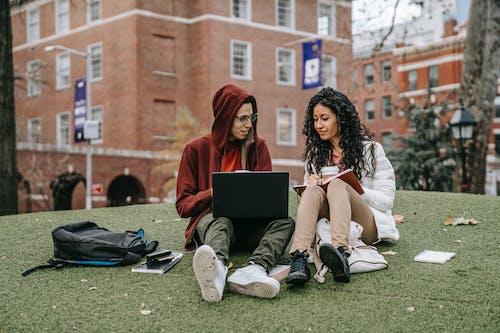 Mulher Com Vestido Branco Sem Mangas Sentada No Campo De Grama Verde Usando Um Macbook
