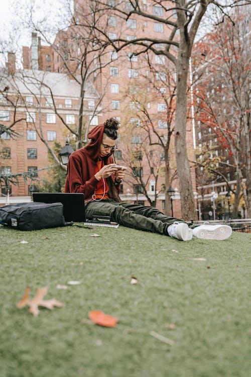 Hombre De Chaqueta Marrón Y Negra Sentado En El Campo De Hierba Verde