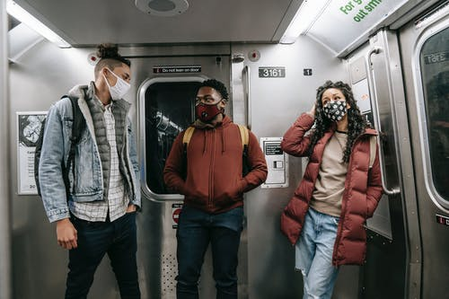 Unrecognizable multiethnic friends in masks standing in subway train