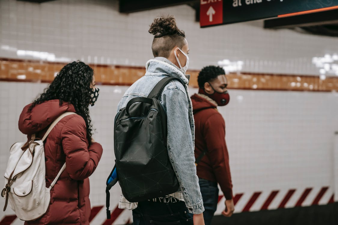 Side view of anonymous young multiracial friends in warm clothes and protective masks with backpacks walking on underground station