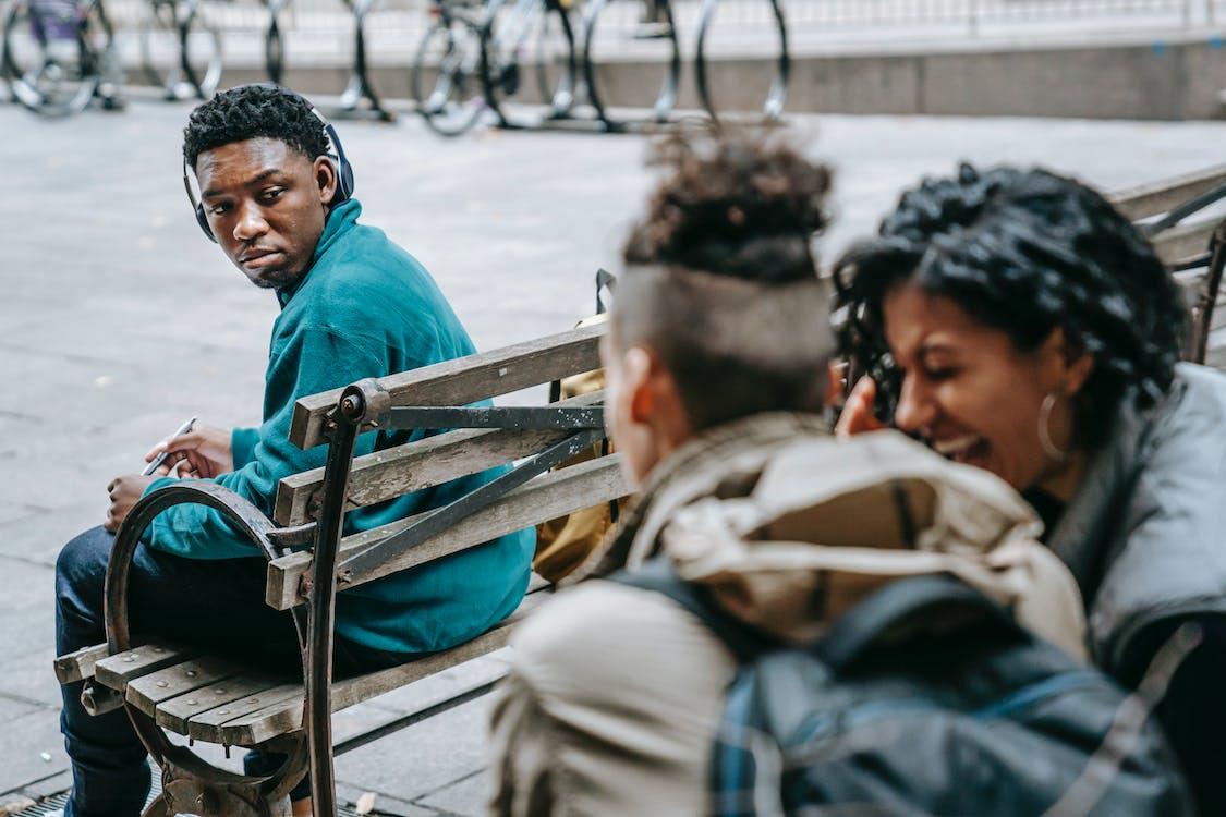 Pria Berkemeja Biru Duduk Di Bangku Kayu Coklat