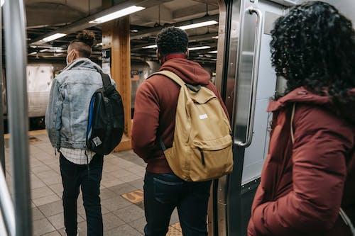 Man in Blue Jacket and Brown Backpack Standing Beside Woman in Black Jacket