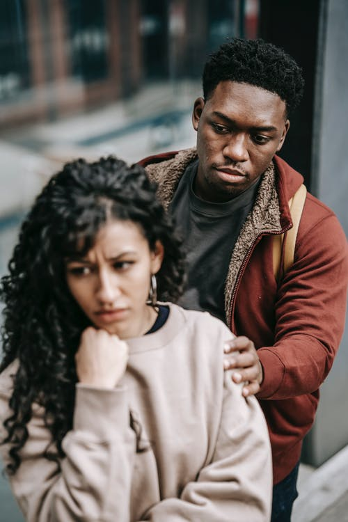 Unhappy young multiracial couple in casual clothes standing in city street while arguing with each other in daylight