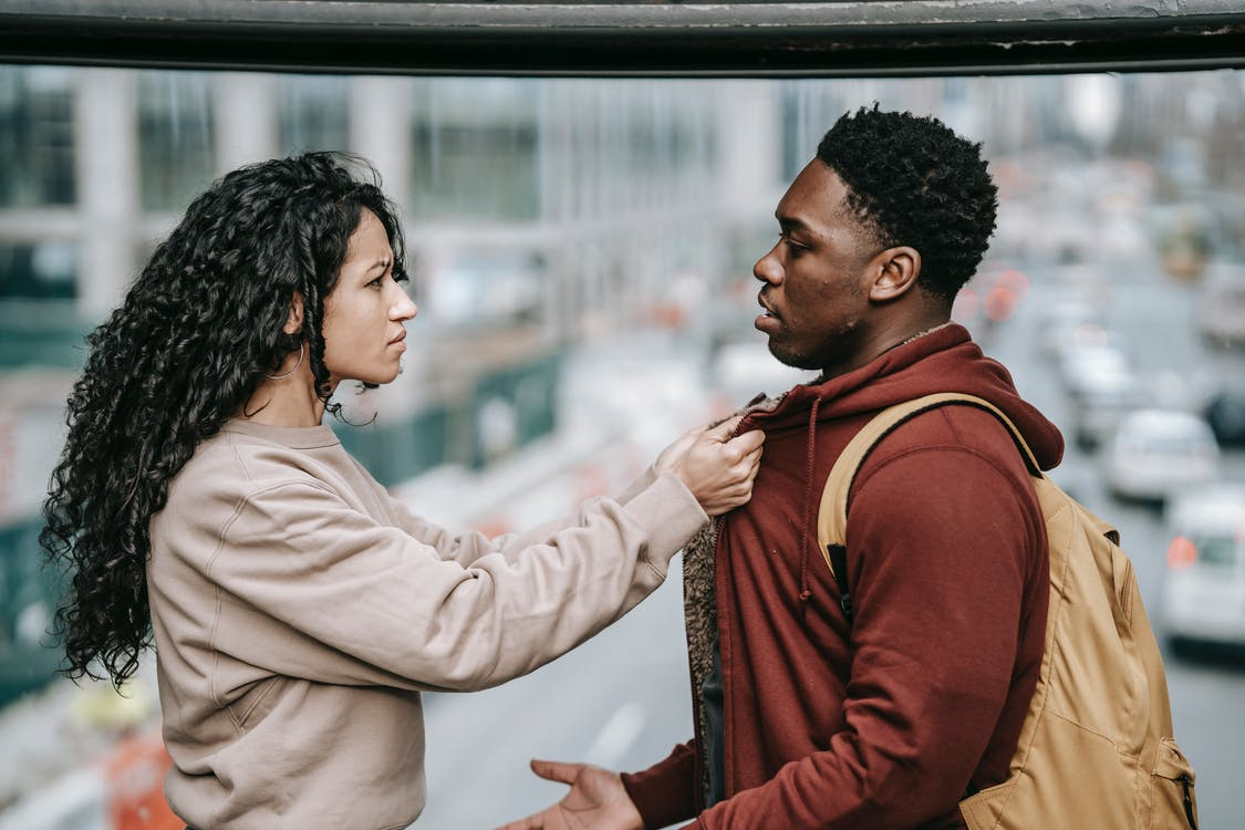Side view of young multiracial couple in casual outfit standing in city street and having argument with each other while woman holding man by jacket and looking at each other