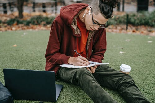 Man studying with notepad and laptop on grassy lawn