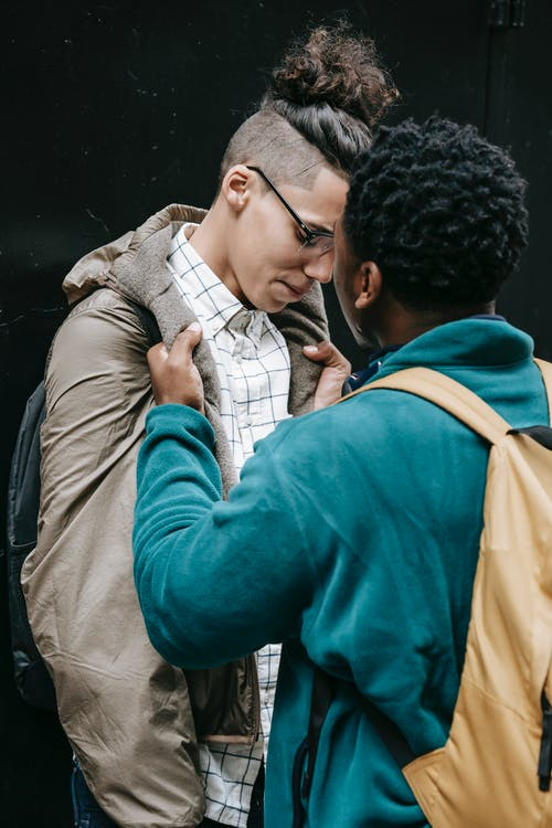 Young African American man in casual outfit and bullying classmate while standing in city street with backpack on black background