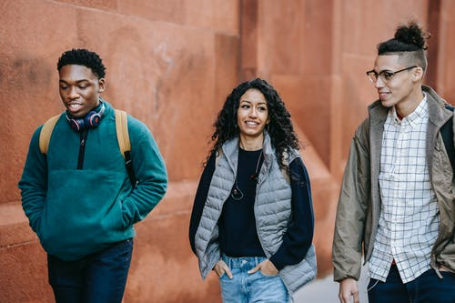 Smiling young multiethnic students in outerwear and backpacks walking in street near red wall with headphones while having conversation in daylight