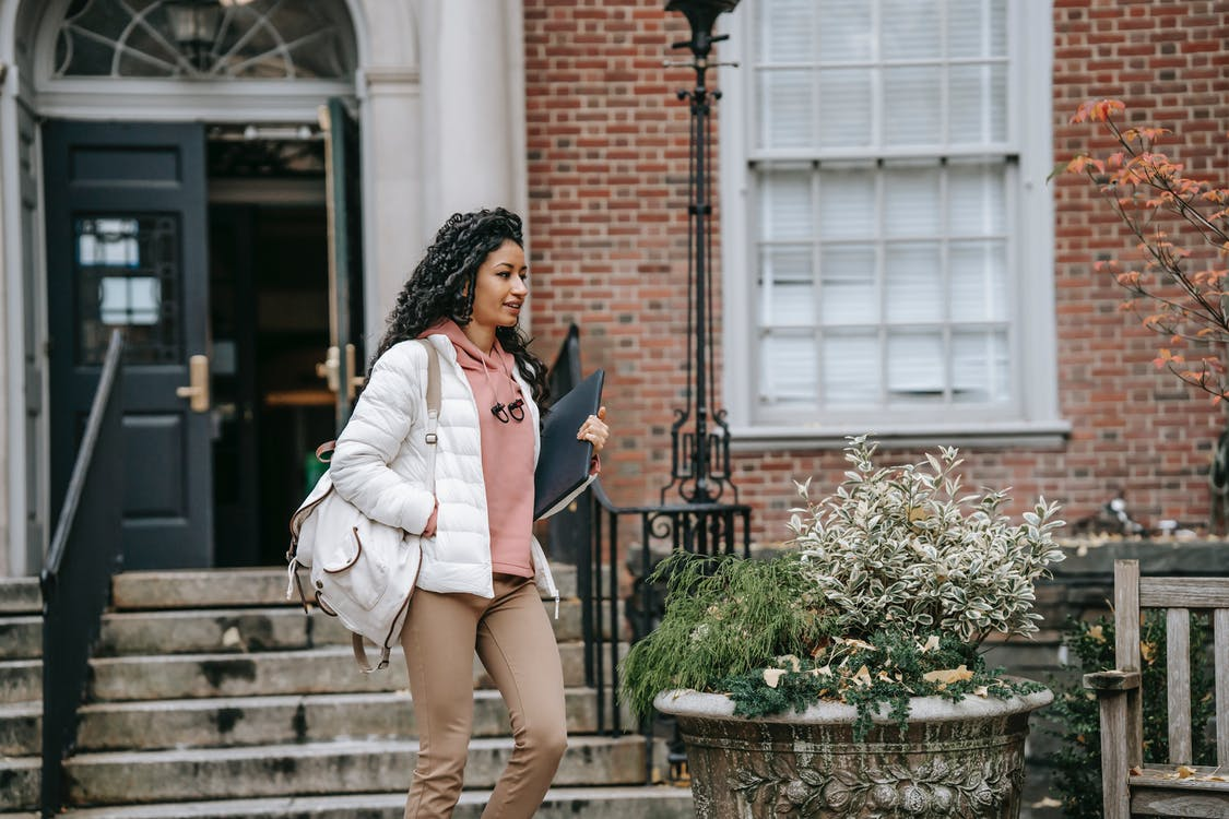 Confident young ethnic woman in warm clothes with backpack walking in city street with folder in daytime near building door and stairs near plant