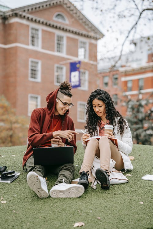 Young multiracial students in outerwear sitting on grass and studying while writing notes in notebook with pen and cup of drink while using netbook in campus in daylight