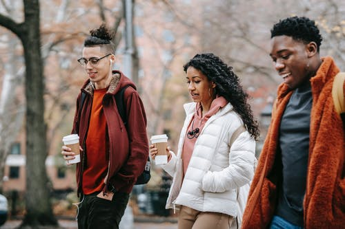 Group of multiethnic students walking on street with coffee cups