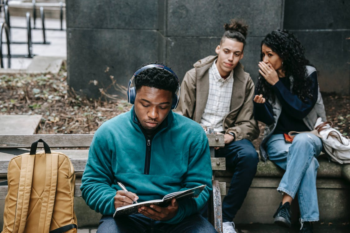 Young multiethnic friends in casual outfit with backpack gossiping behind back of African American guy sitting on bench in headphones and taking notes in notebook in city street in daylight